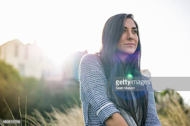 Young woman with long brown hair in sunlight
