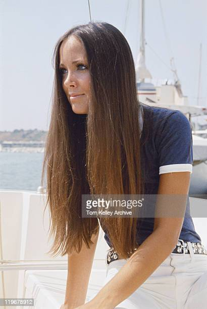 Young woman with long brown hair sitting in boat, close-up, smiling