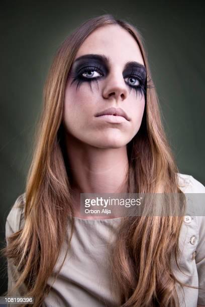 Young Woman With Long Fake Eyelashes and Dark Make-Up Posing