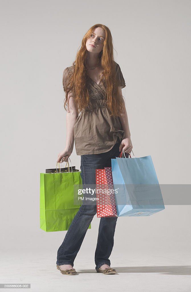 Young woman with long ginger hair, carrying shopping bags, looking aside : Stock Photo