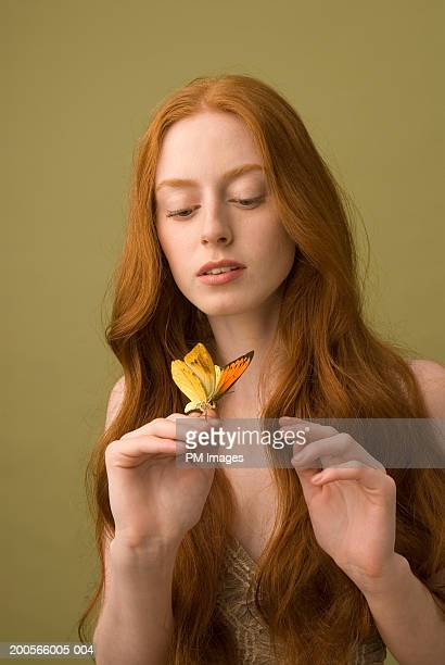 Young woman with long ginger hair, holding and looking at butterfly