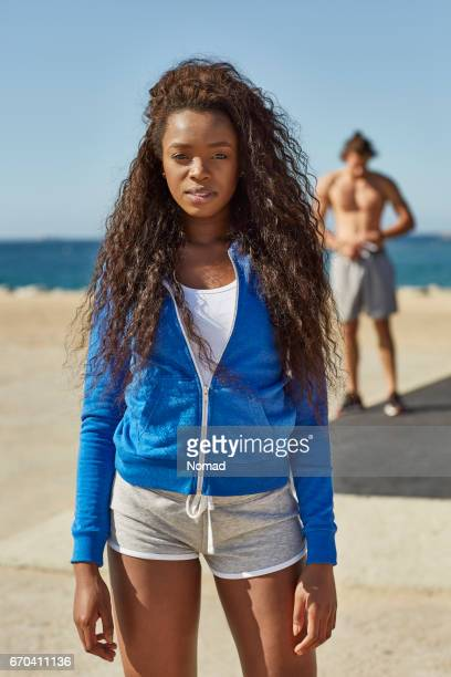 Young woman with long hair in sportswear at beach
