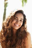 young woman with long hair smiling at camera