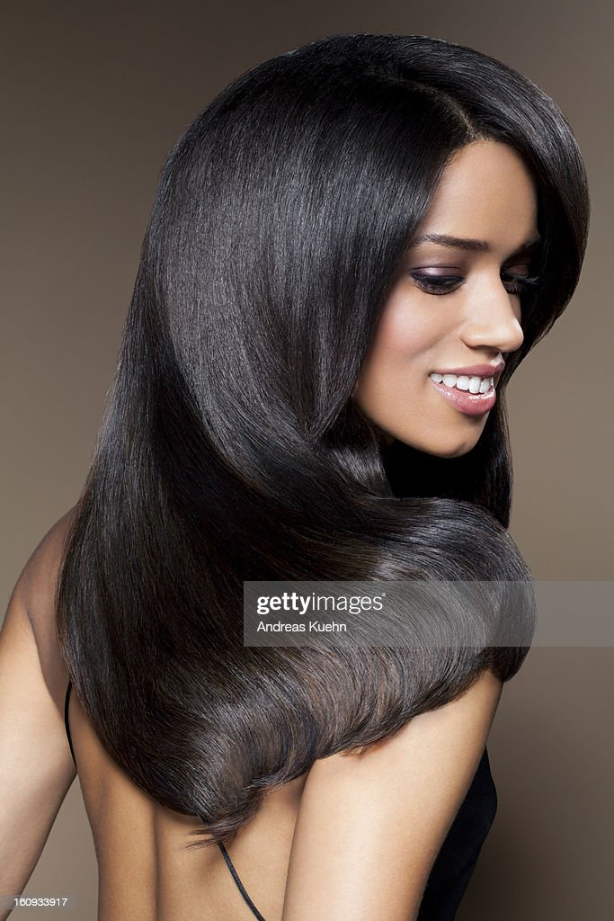 Young woman with long, shiny hair smiling. : Stock Photo