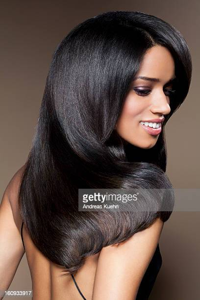 Young woman with long, shiny hair smiling.