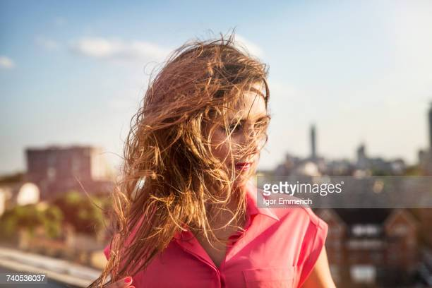 Young woman with long windswept hair at roof party in London, UK