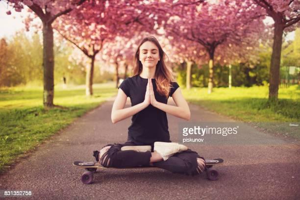 Junge Frau mit Longboard in Kirschblüte Gasse