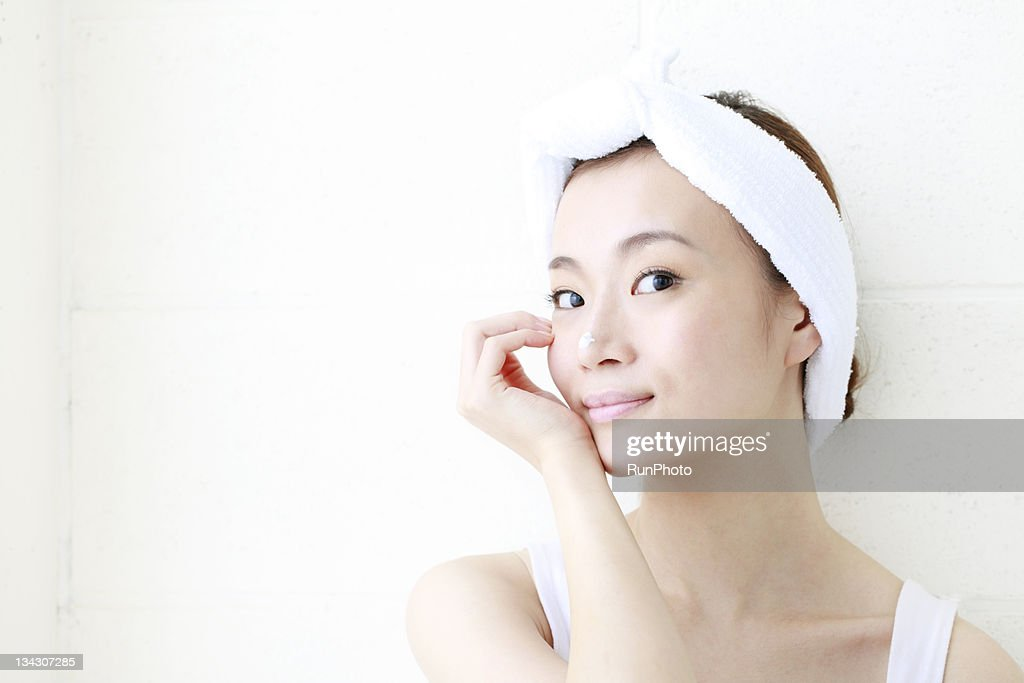 young woman with lotion on nose,smiling : Stock Photo
