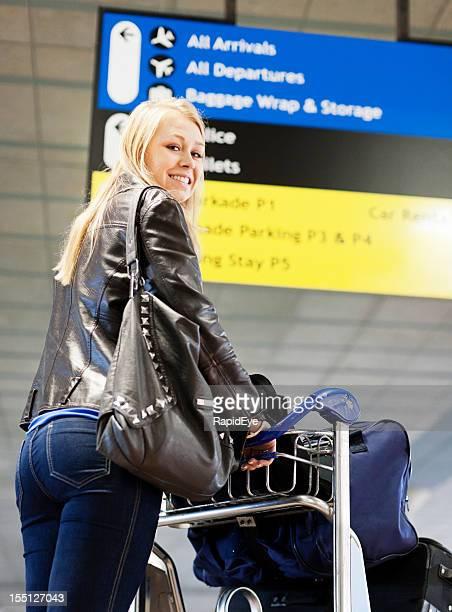 Jeune femme avec bagages panier souriant à l'entrée de l'aéroport