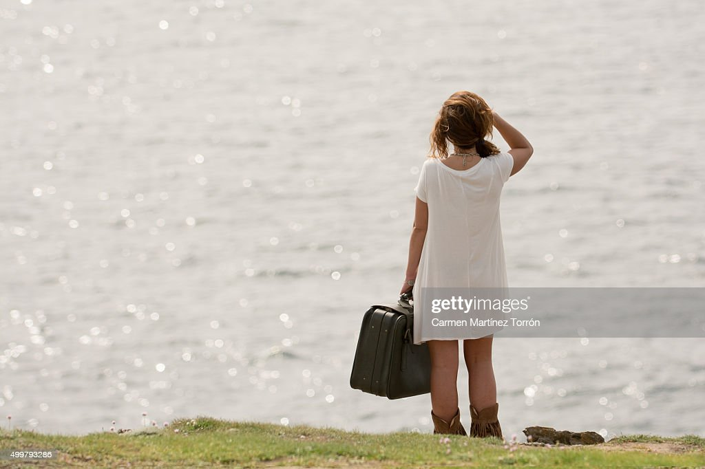 Young woman with luggage standing in hill, rear view : Photo