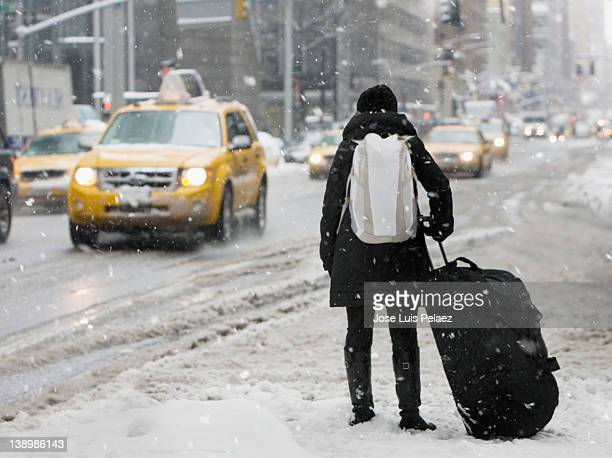 Young woman with luggage waiting for a cab