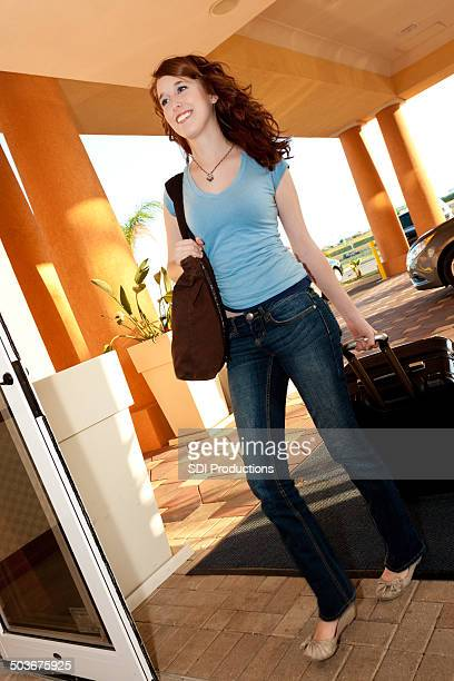 Young woman with luggage walking into hotel