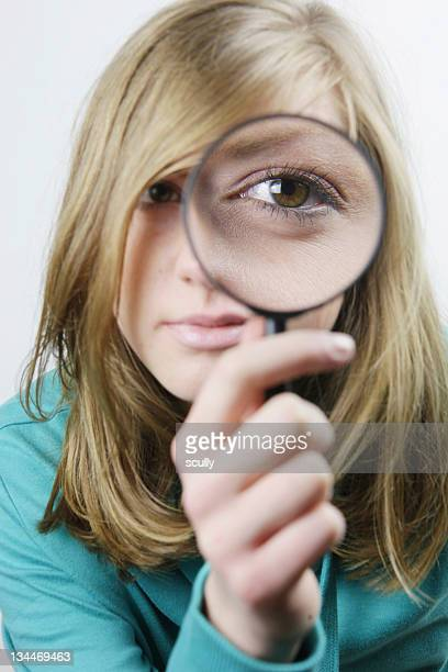 Young woman with magnifying glass in front of her eye
