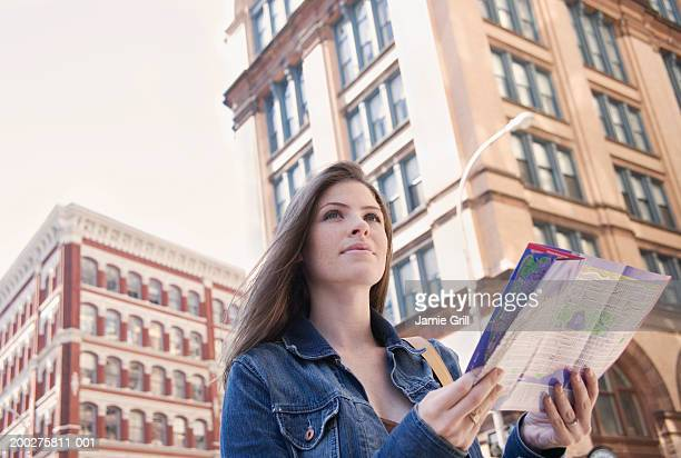 Young woman with map, buildings in background