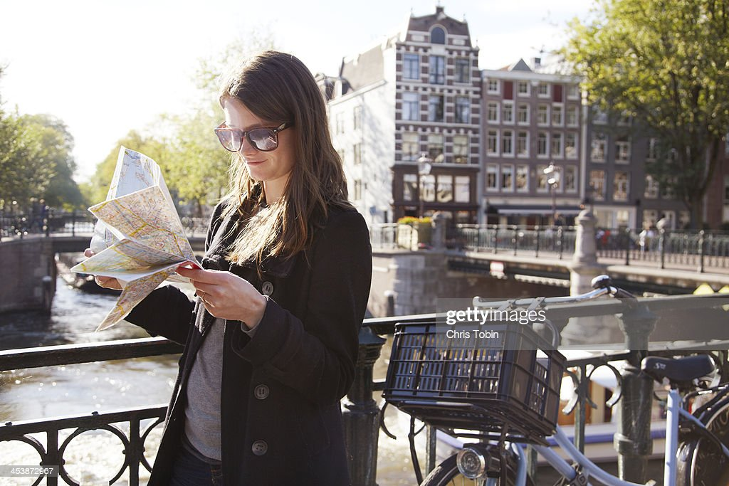 Young woman with map on bridge at canal : Stock Photo