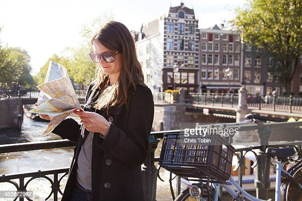 Young woman with map on bridge at canal