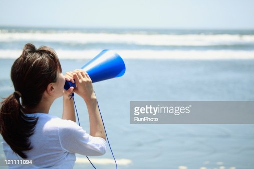 young woman with megaphone on the beach : Stock Photo