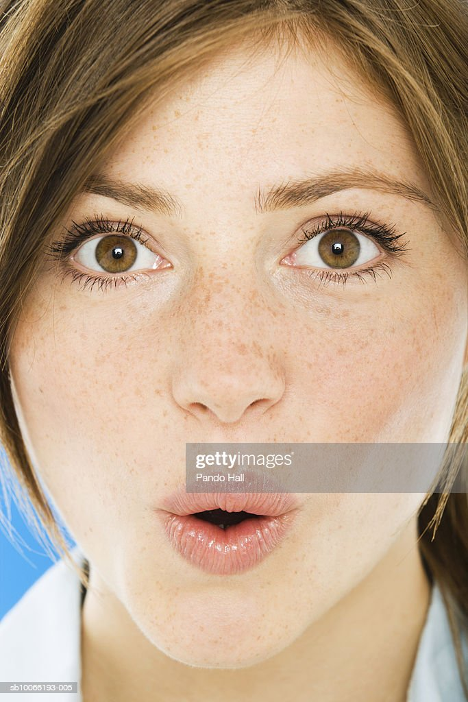Young woman with mouth open and raised eyebrows, portrait, close-up : Stock Photo
