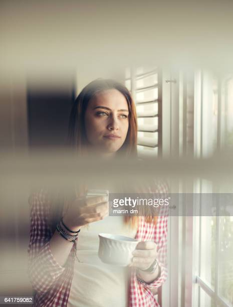 Young woman with mug looking through the window