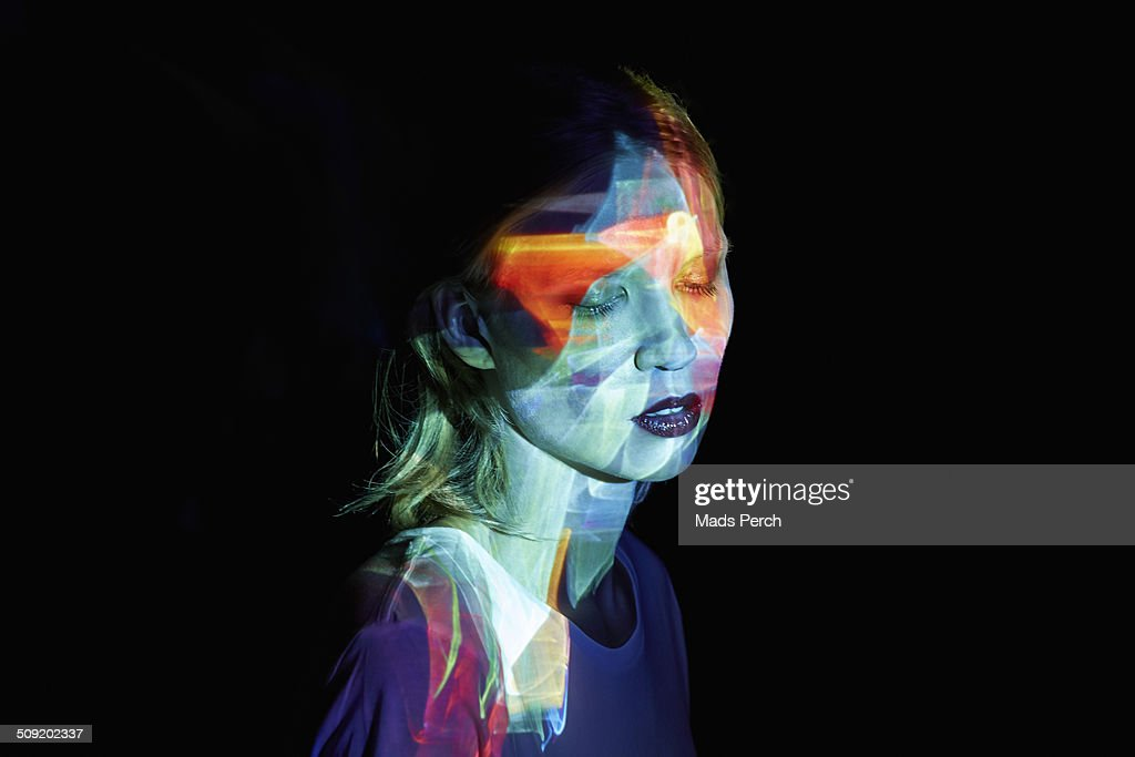 Young Woman with Multicolored Light in her Face : Stock-Foto
