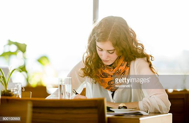 Young woman with note-book writing in cafe