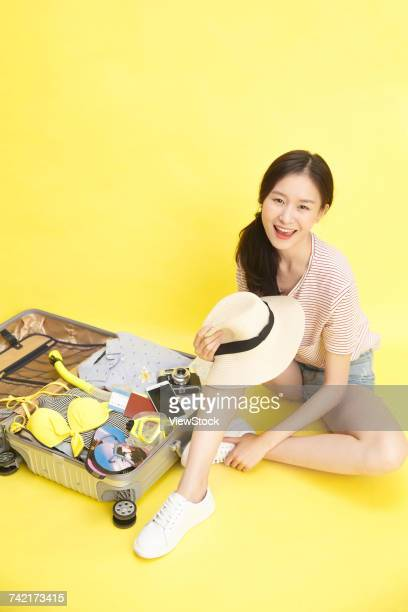 Young woman with opened suitcase