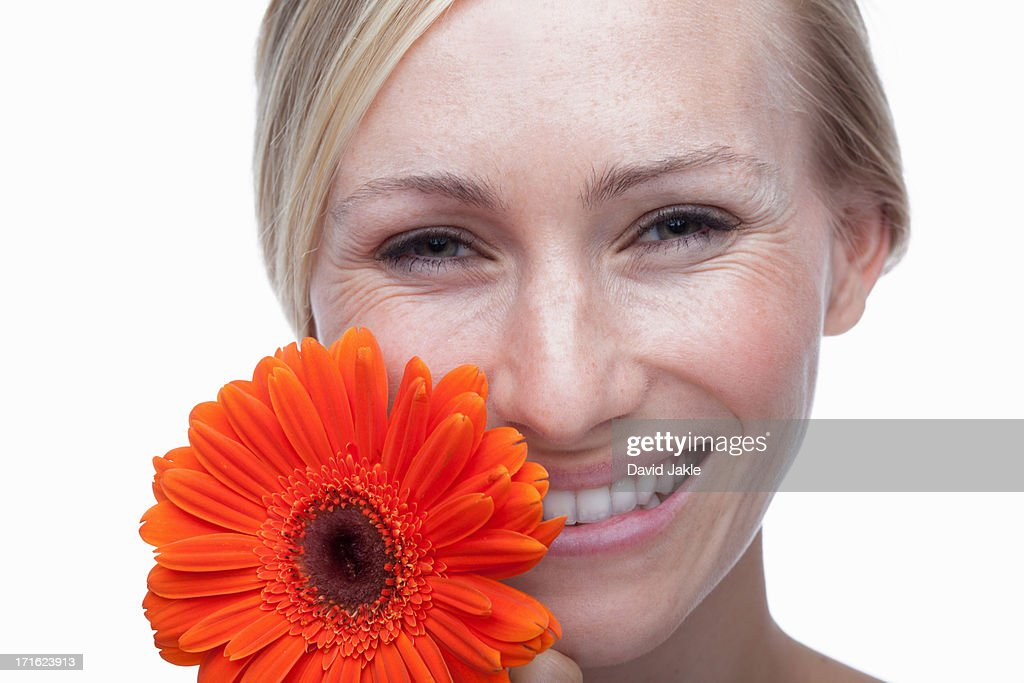 Young woman with orange flower : Stock Photo