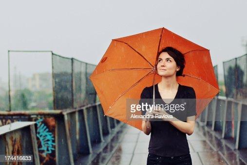 young woman with orange umbrella in the rain