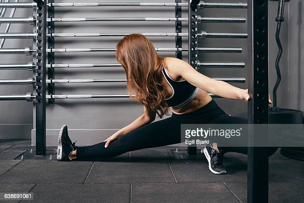Young woman with outstretched leg in warm up exercise at gym