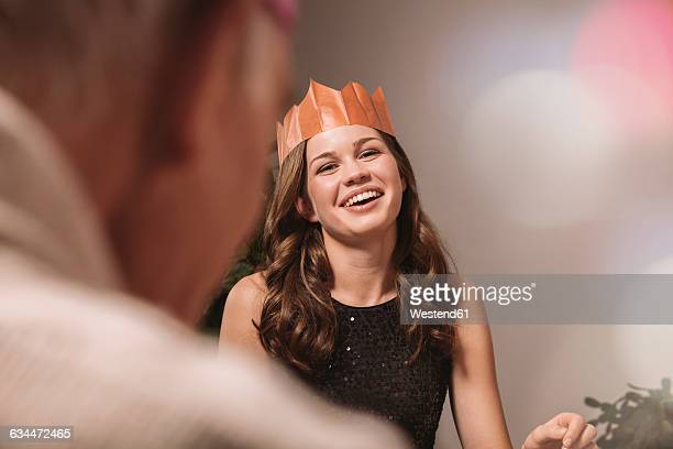 Young woman with paper crown laughing