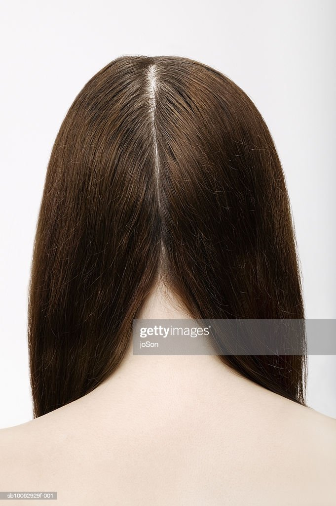 Young woman with part in long brown hair, rear view : Stock Photo