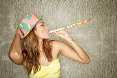 Young woman with party hat and noisemaker, portrait