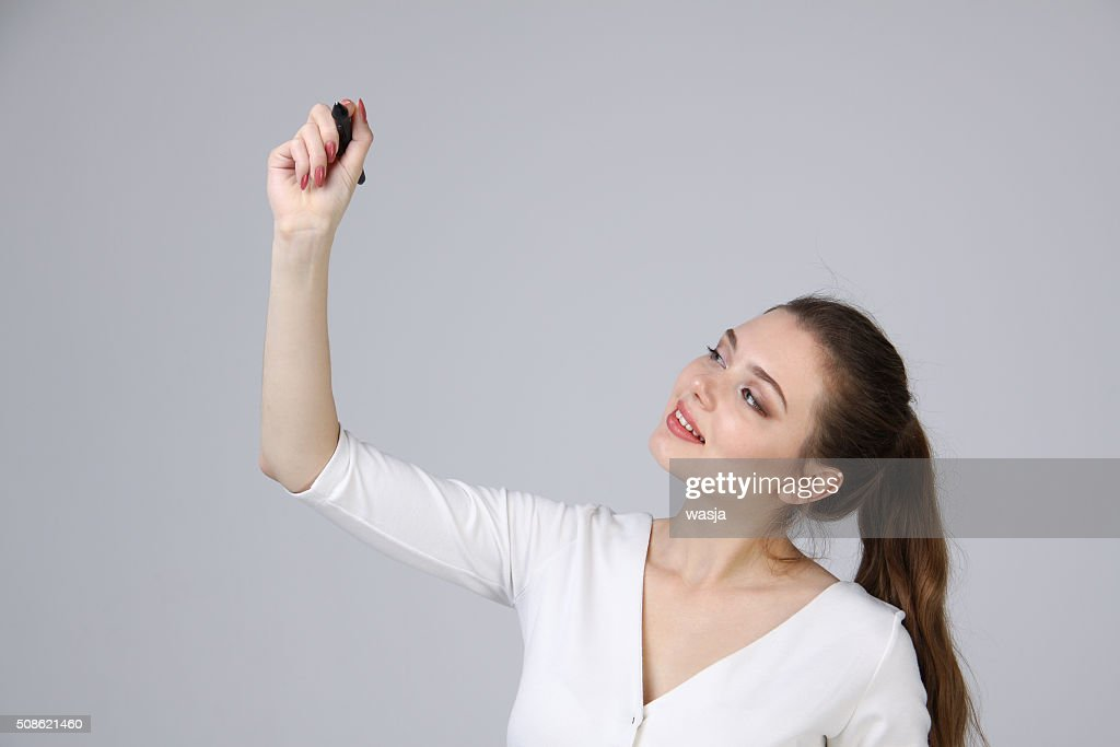 young woman with pen on grey background : Stock Photo