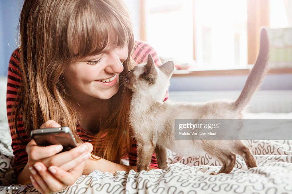 Young woman with phone gets cuddles from kitten. : Stock Photo