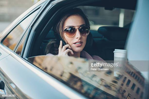 Young woman with phone on the back seat