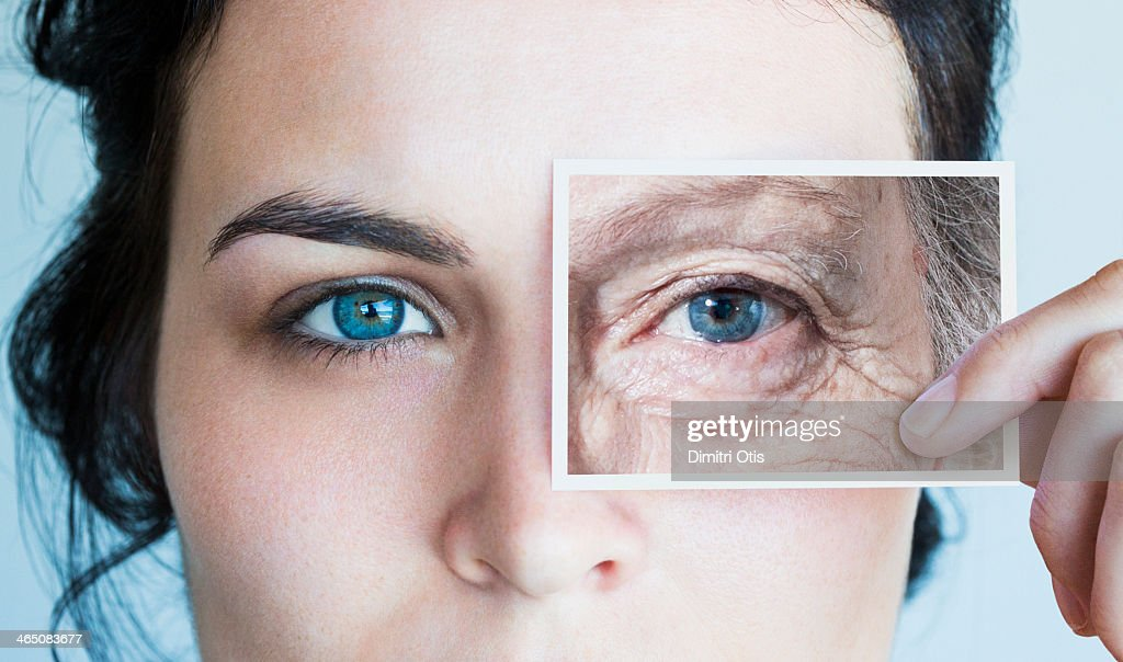 Young woman with photo of aged eye over her own : Stock Photo
