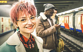 Young woman with pink hair and group of multiracial hipster friends waiting for train at tube subway station - Urban friendship concept with young people standing together in city underground area