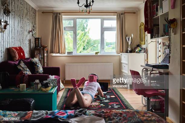 Young woman with pink hair lying on carpet wearing headphones and using laptop at home