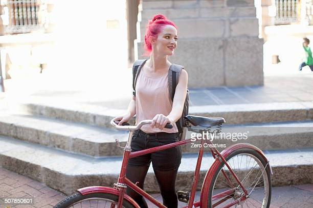 Young woman with pink hair pushing her bicycle in city