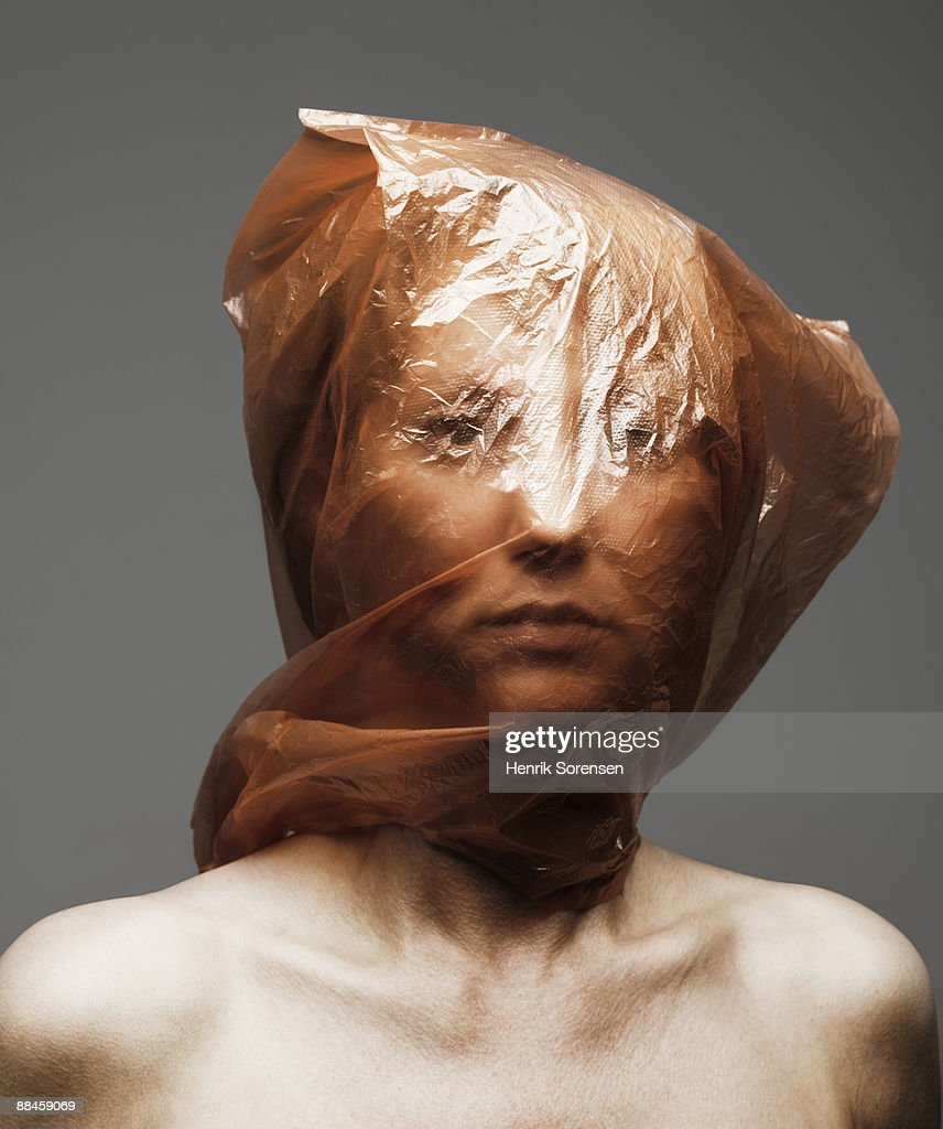 Young woman with plastic bag over her head : Stock Photo