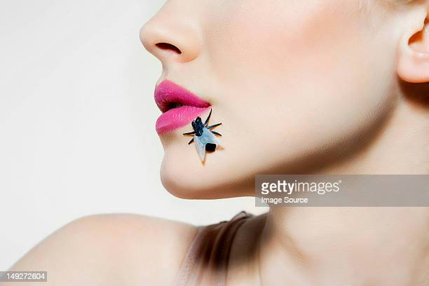 Young woman with plastic fly on face