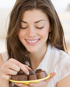 Young woman with plate of chocolates, smiling, close-up