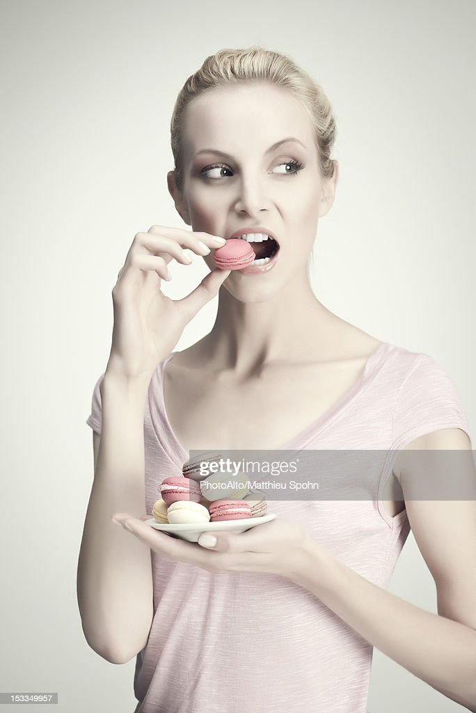 Young woman with plate of macaroons, portrait