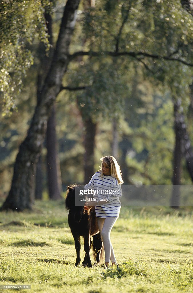 Young woman with pony in field : Stock Photo