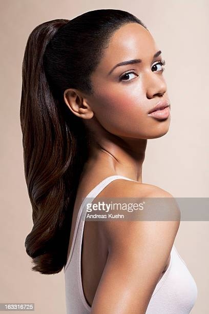 Young woman with pony tail looking over shoulder.
