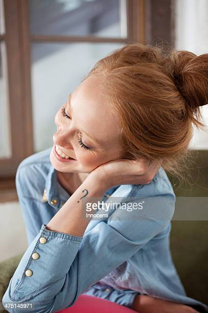 Young woman with question mark tattoo smiling