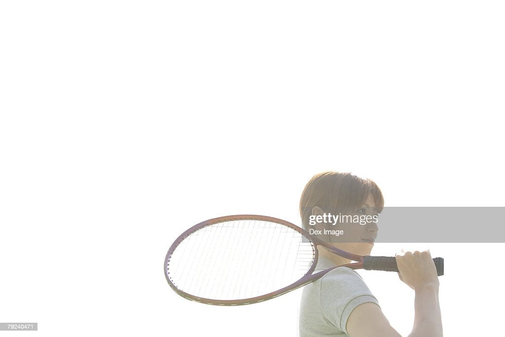 Young woman with racquet resting on her shoulder : Stock Photo