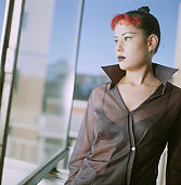 Young woman with red hair looking out of office window, portrait