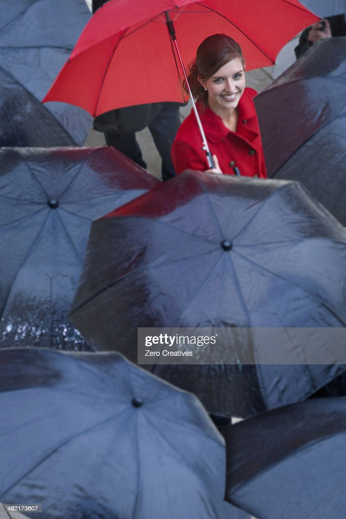 Young woman with red umbrella amongst black umbrella's : Stock Photo