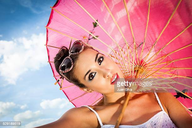 Young woman with red umbrella and sunglasses